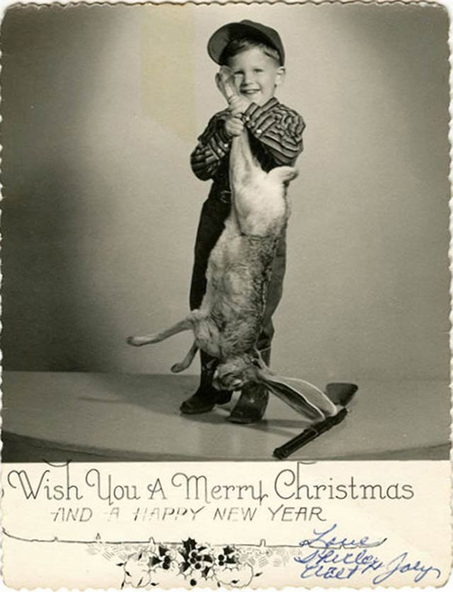 Nothing screams the holidays like a kid and his a dead rabbit! ~ Funny Family Christmas Photos ~ vintage Christmas card of boy holding dead rabbit he shot
