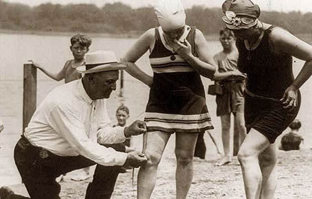 An authority measuring the length of a woman's swimsuit in 1922 along the Potomac River in Washington, D.C. Women were arrested if their suit was deemed immodest.