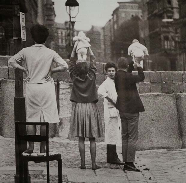 Residents of West Berlin in 1961 showing off their children to their grandparents who live on the eastern side.