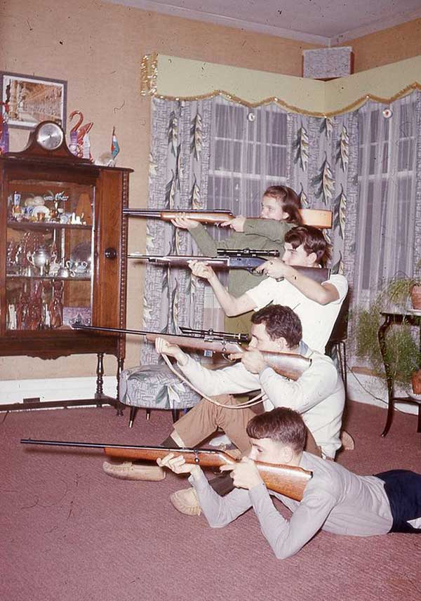 31 Funny Awkward Family Photos ~ vintage snap 1950s family with guns rifles in living room
