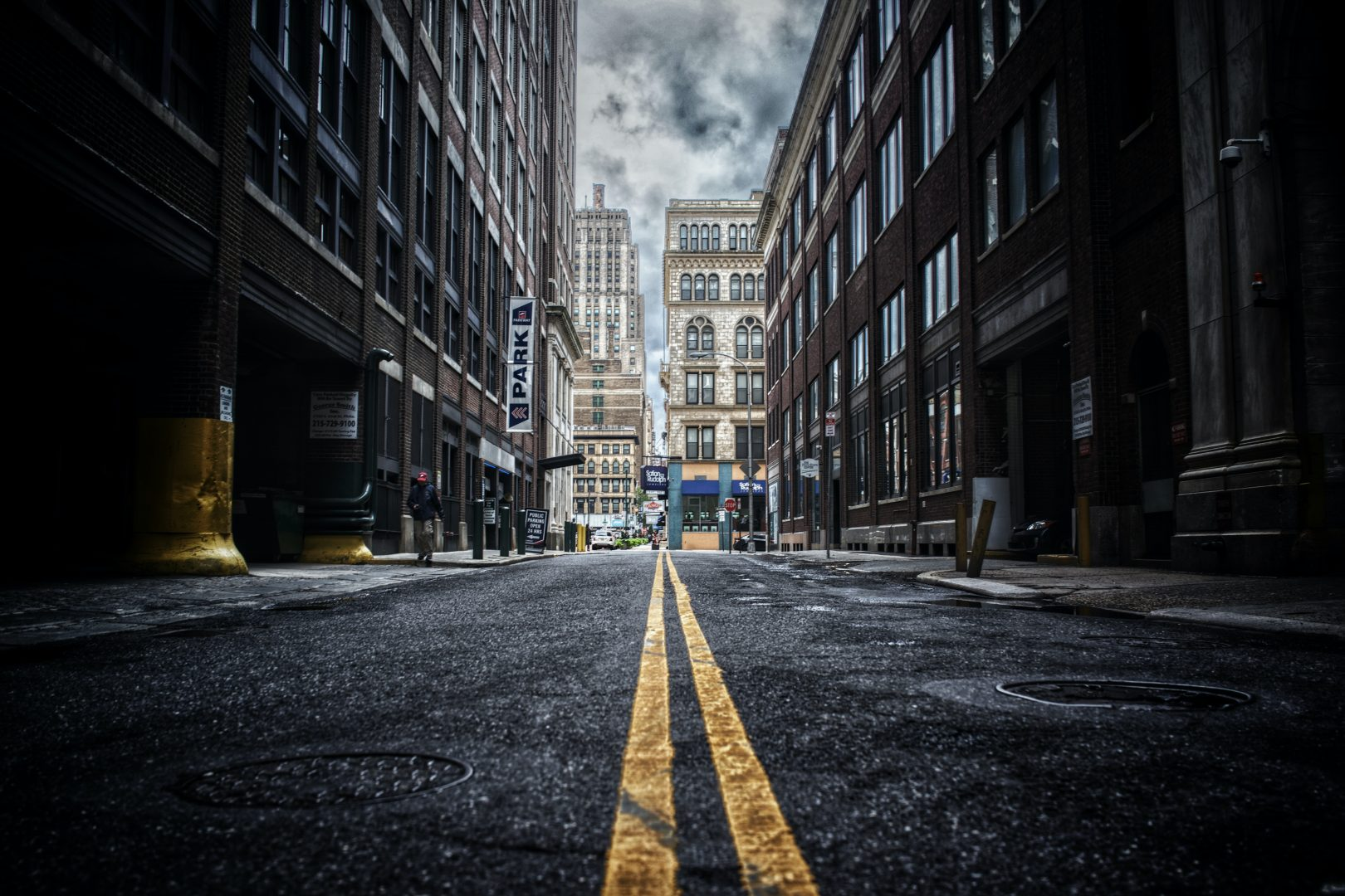 low-angle photo of street between two brown concrete buildings