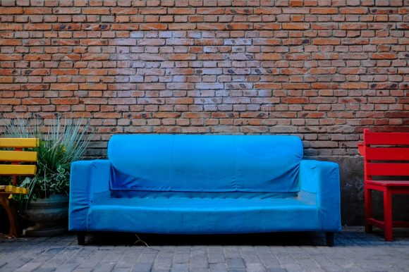blue couch beside brown brick wall