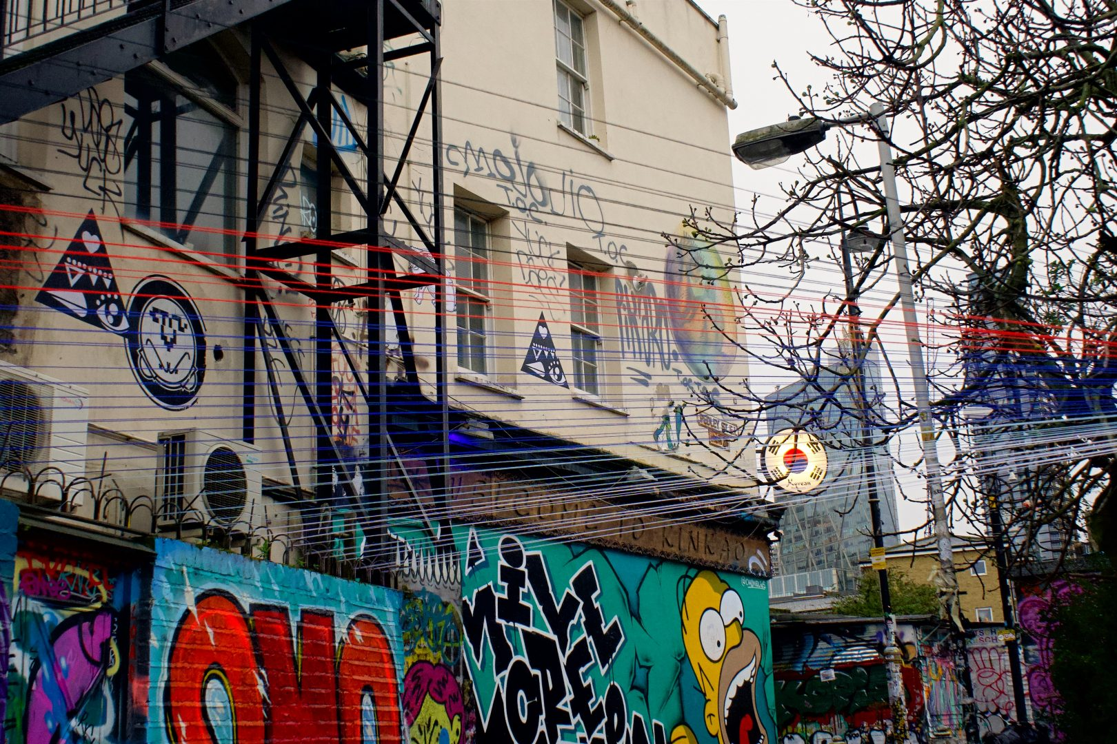 graffiti on wall near bare tree during daytime