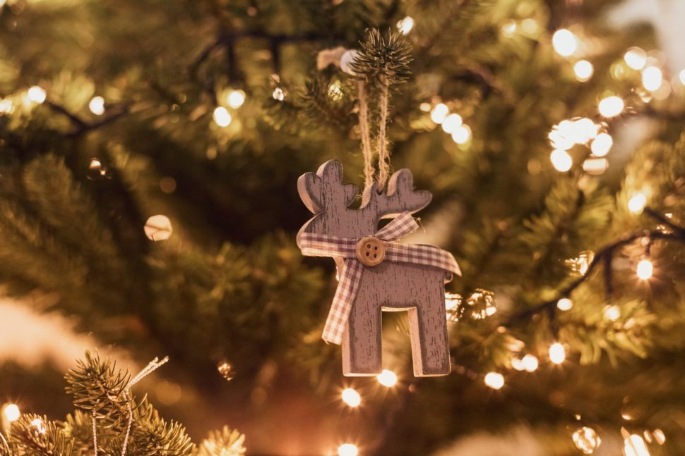 selective focus photo of brown deer ornament on Christmas tree with turned-on string lights