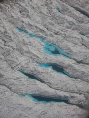 Crevasses filled with blue water.