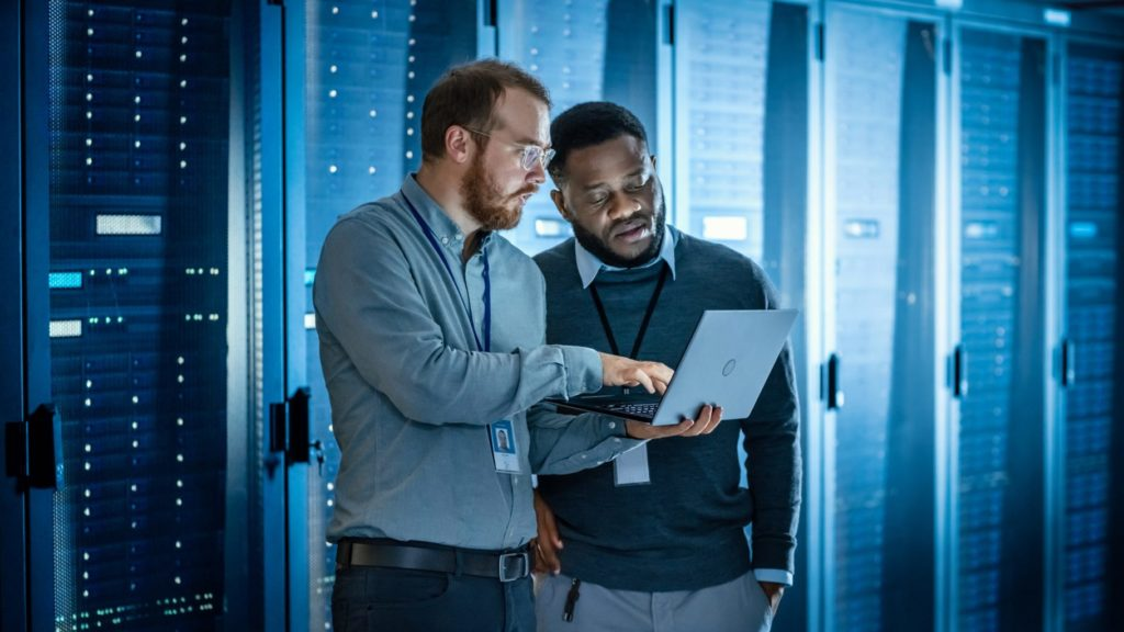 Caucasian Data Center Worker and African American Data Center Worker discussing project