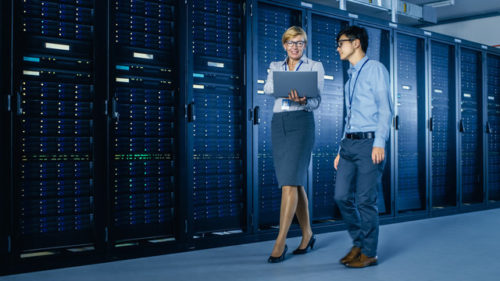 man and woman walking in data center talking about data center relocation consultants