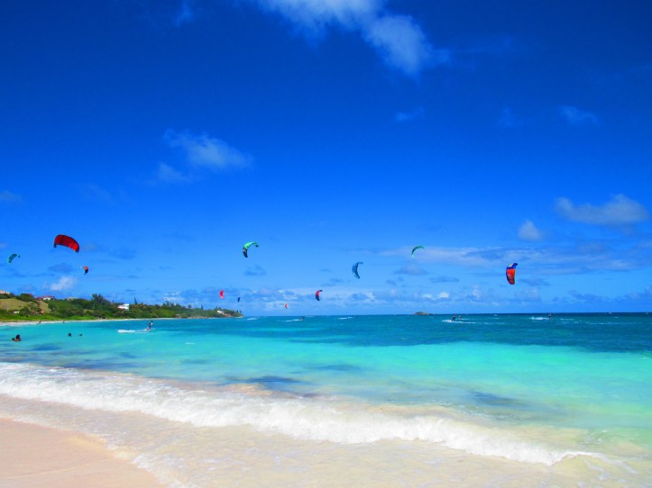 Many colorful kiteboard kites flying over the turquoise water of Jabberwock beach in Antigua