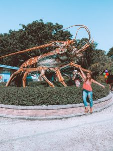 girl standing in front of a giant spiny lobster statue in Islamorada