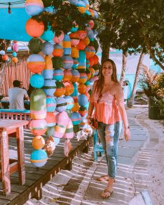 girl standing in front of colorful buoys hanging at the Islamorada Brewing Company