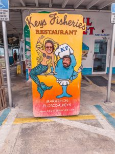 couple taking a photo through a face-in-hole board as a mermaid and a fish at the Keys Fisheries restaurant