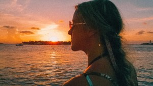 girl standing in front of the sunset, profile view, at mallory square in key west
