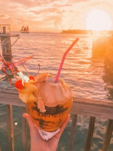holding a coconut drink in front of the sunset in key west with a sailboat in the background