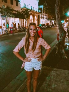 girl standing on Duval street in key west wearing a light pink shirt and white shorts with a rainbow macaw on her shoulder