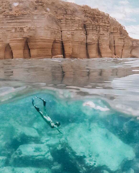 girl snorkeling below the pillars of Hercules in Antigua
