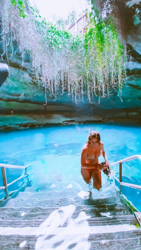 girl walking out of natural underground spring using aluminum steps