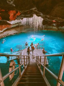 Stairway leading to natural underground spring with crystal clear water and people snorkeling