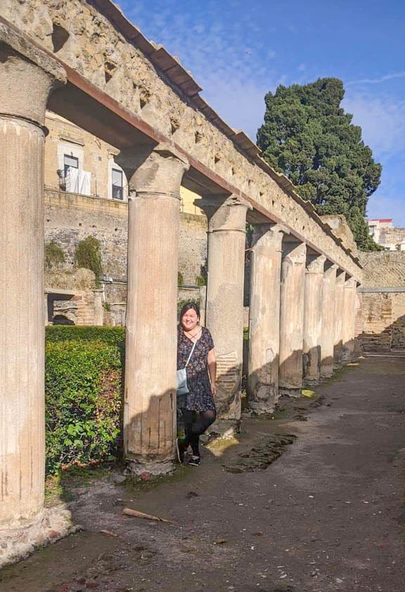 Riana standing by the columns at Herculaneum