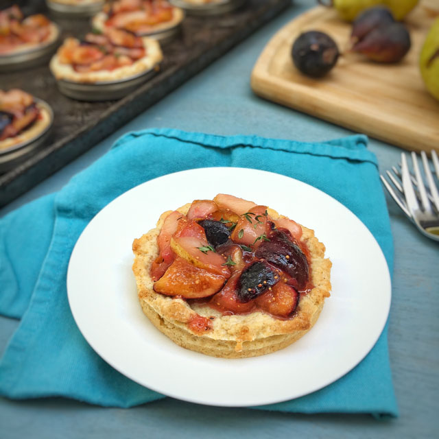 Use Mason jar lids to make portion sized fruit pies like these mini pear and fig tarts! Recipe at Teaspoonofspice.com #healthykitchenhack #minidesserts #fruittarts #figs #pears