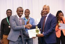 Safaricom Chief Corporate Affairs Officer, Stephen Chege presents a trophy and certificate to Stephen Muchiri Waithanji, a recent JKUAT graduate who emerged the winner during the My Little Big Thing Innovation Challenge