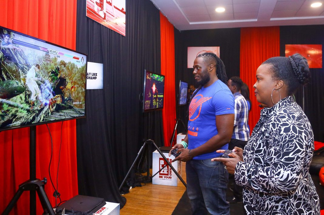 Safaricom Senior Manager Youth Segment Angela Githuthu (Left), Battle it out in a combat play station game with Blaze mentor and professional gamer Brian Diang'a during the Safaricom Blaze e-sports tournament launch.
