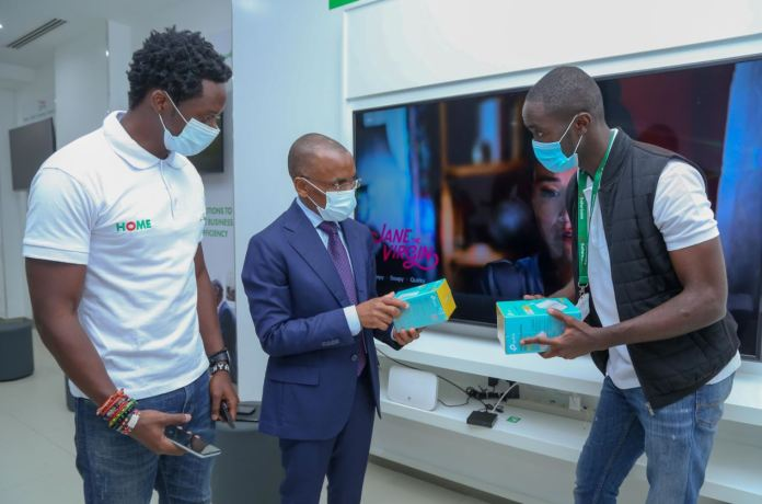 Safaricom Chief Executive Officer Peter Ndegwa, is being taken through the MASOKO products by Dennis Ochieng and Brian Alindi, on how they are used and are now accessible at the shop during the launch of the new Safaricom shop in Moi Avenue.