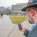 Image of man on campus with mobile phone