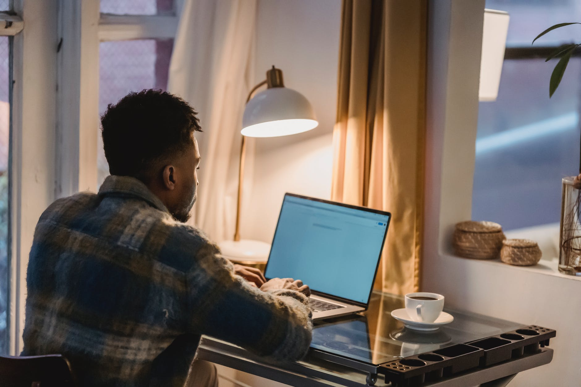 focused black man using laptop in evening at home