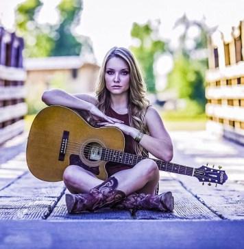 guitar-country-girl-woman-musician-sitting-bridge-ground-looking-at-camera