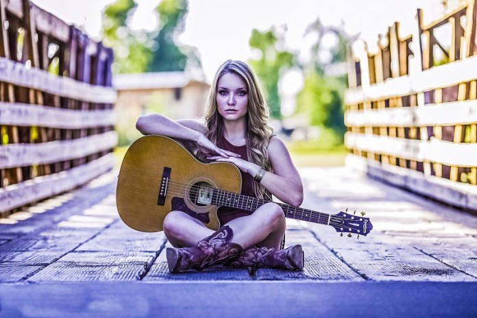 guitar-country-girl-woman-musician-sitting-bridge-ground-looking-at-camera