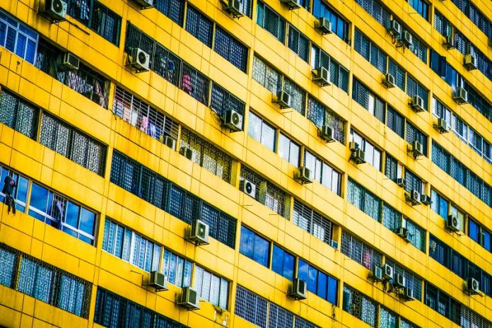 Apartment Building Yellow Wall AC Air Conditioner Units Hanging Summer Urban