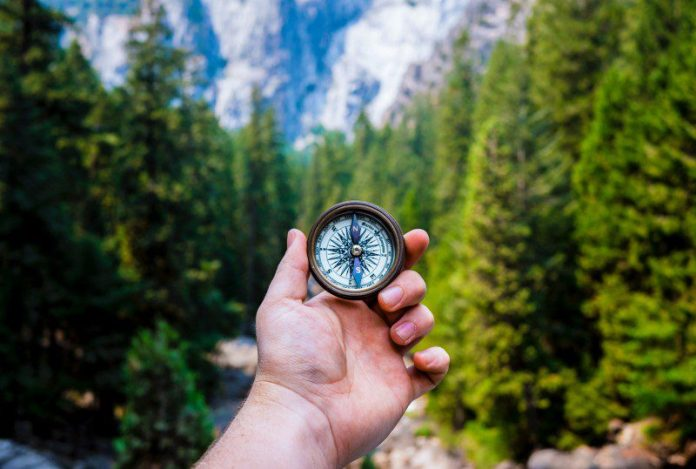 Navigation Compass In Hand Forest Hiking Cloud Mountains ITSM ITIL DevOps Computing Foundation Guide Enterprise Digital Transformation