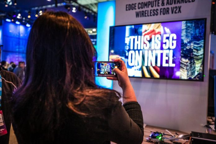 MWC Photo This Is 5G On Intel Apple Acquisition Smartphone Modem Tech Acquired Woman Takes Snapshot With Mobile Phone At Event News