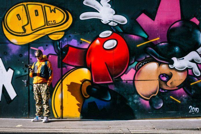 Evil Mickey Mouse Graffiti Mural Wall Man Standing Smartphone Social Media Warfare Fake Follower Bot Attack