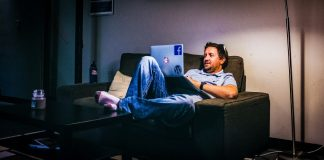 Man Sitting On Couch With Laptop Digital Entertainment Peak During Coronavirus COVID-19 Outbreak