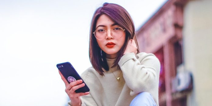 Pros-and-Cons-of-Playing-Games-on-Mobile-Phone-Woman-Using-Smartphone-Looking-Fashion-Glasses-Person