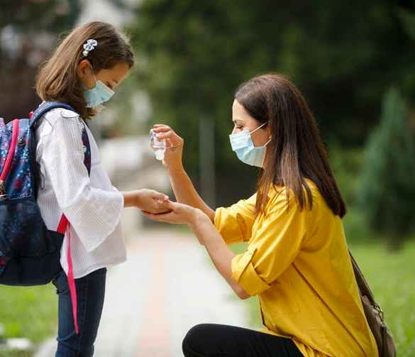 masked mother helps masked daughter in backpack with hand sanitizer