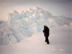 A person standing on an ice chunk with a large ridge of ice in front of them.