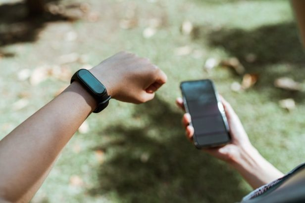 crop faceless person showing smart watch while using smartphone outdoors