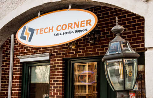 picture of the tech corner storefront with sign hanging under opening archway