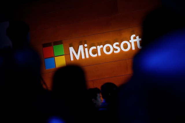 The Microsoft logo is illuminated on a wall during a Microsoft launch event