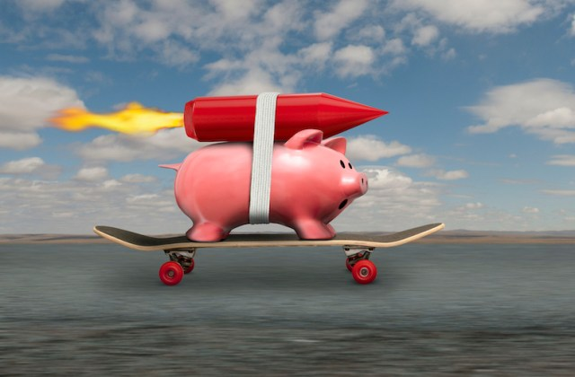 A piggy bank streaks down the road to riches on a skateboard and with a rocket strapped to his back.