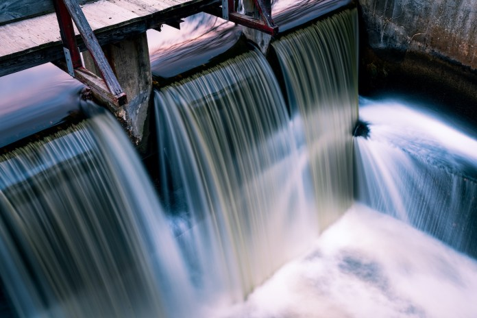 Long exposure spillway shines water and light. Copy space.