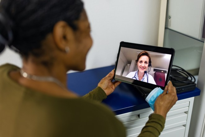 Woman having a medicine video conferencing with her doctor using digital tablet. Senior woman on a video call with a doctor using her tablet computer at home.