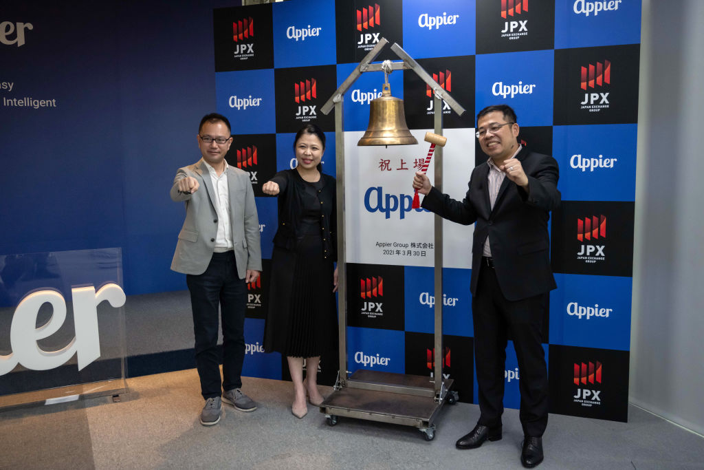 Chih-Han Yu, chief executive officer and co-founder of Appier Group Inc., right, holds a hammer next to a bell during an event marking the listing of the company on the Tokyo Stock Exchange, at the company's office in Taipei, Taiwan on Tuesday, March 30, 2021. Photographer: Billy H.C. Kwok/Bloomberg via Getty Images