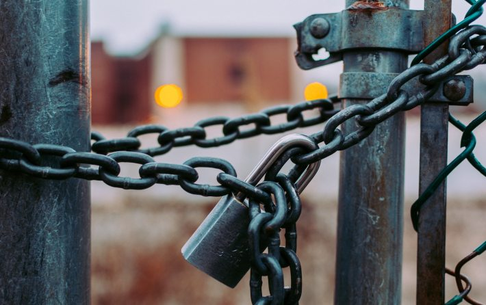 A padlocked chain holds a fence or gate closed