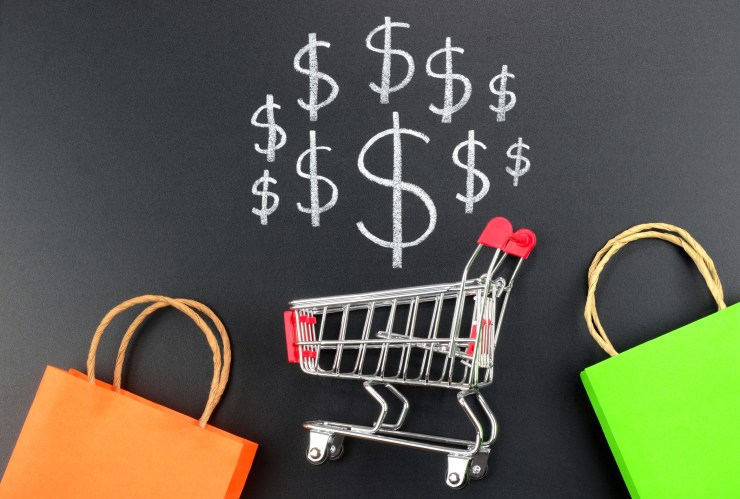 Shopping cart with dollar sign and colorful shopping bags.