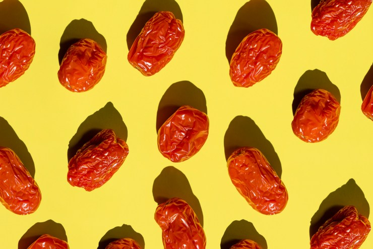 Directly above view of some rotten cherry tomatoes on Yellow background