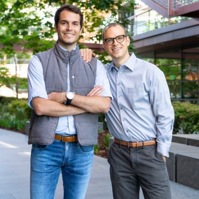 Orestis Vardoulis, left, and Urs Naber, co-founders of Zeit, pose with each other in a courtyard.