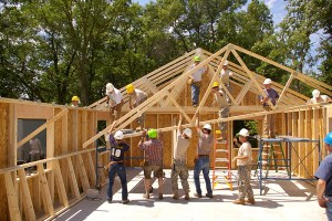 U.S. Army soldiers, along with volunteers from the community, install roof trusses for a Habitat for Humanity home in Brainerd, Minn., July 13, 2010